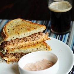A patty melt sandwich cut in half on a plate