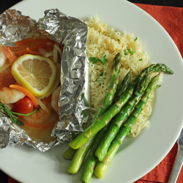 A plate with shrimp packet, asparagus, and rice