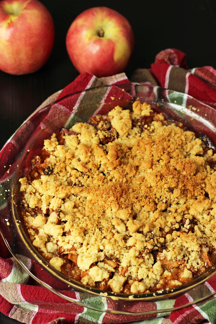 apple crisp in pie plate with red and green napkin and apples
