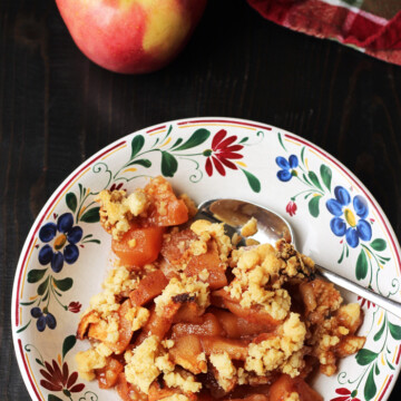 A plate of apple crisp, with whole apple