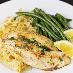 plate of fish, buttered noodles, green beans, and lemon slices
