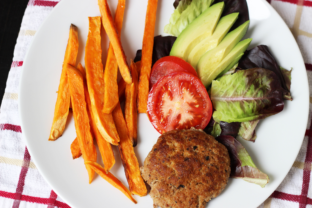 Sweet Potato Fries on a plate with a burger and a salad