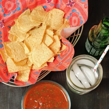 A bowl of salsa with basket of chips