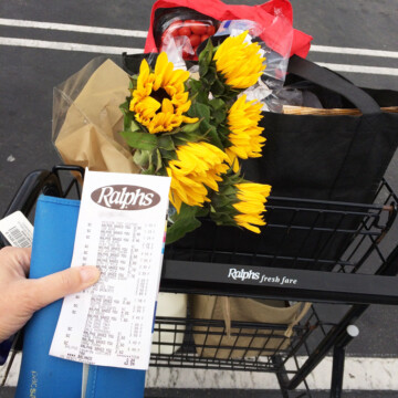 holding receipt and wallet and shopping cart