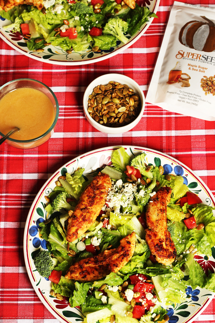 A lunch table set with salad, dressing, and toppings