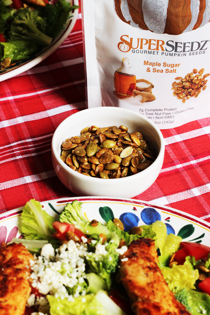 bowl of Pumpkin seeds next to salad
