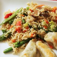 vegetable fried rice on plate with potstickers