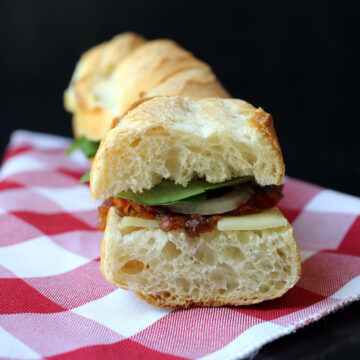 cheese and pickle baguette sandwich on a red checked cloth.