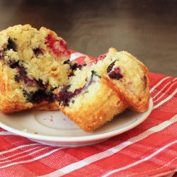 split berry muffin on saucer on red cloth