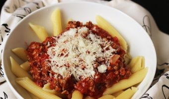 A bowl of pasta with meat sauce with cheese