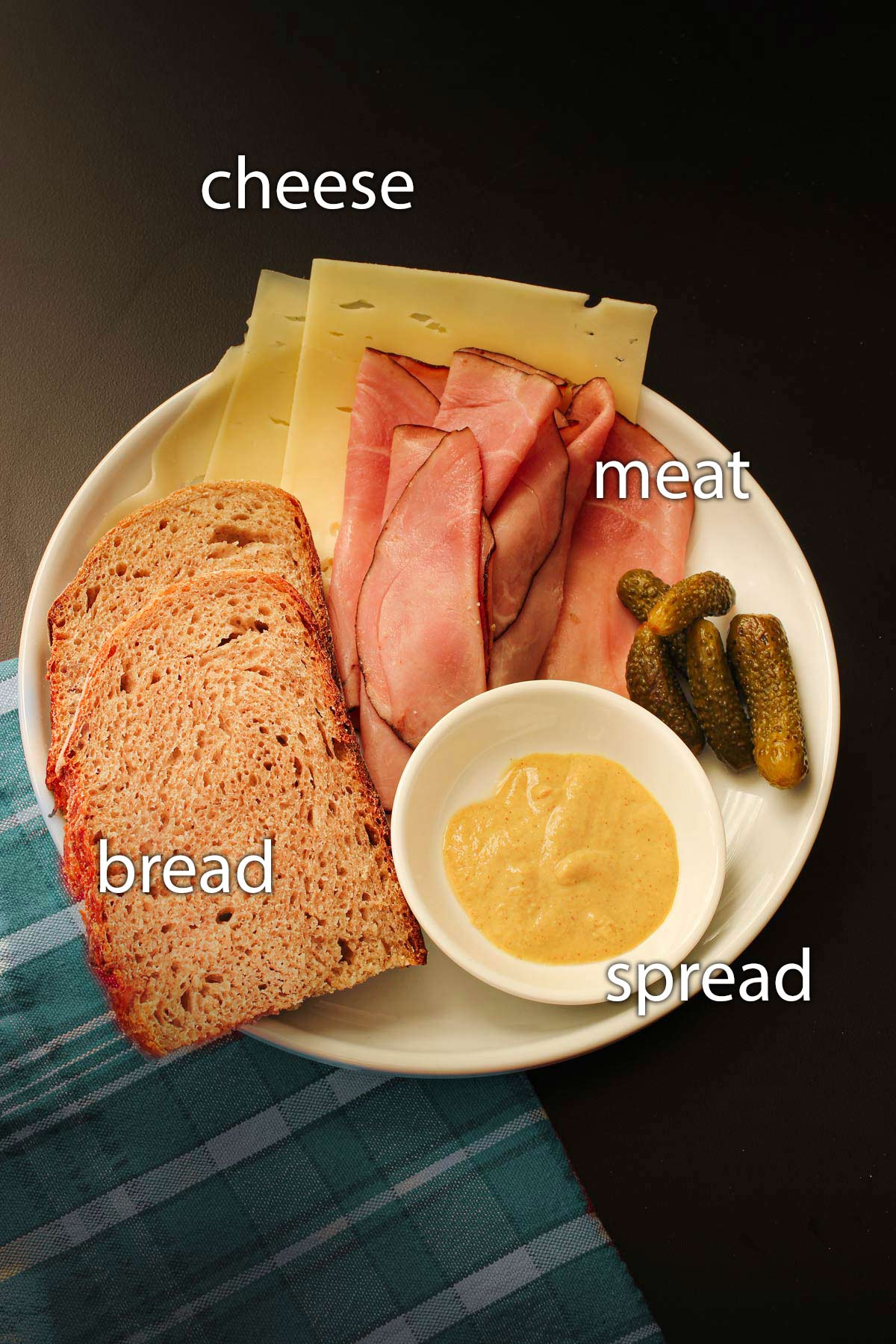 white plate with an array of sandwich ingredients, including bread, cheese, ham, mustard, and pickles.