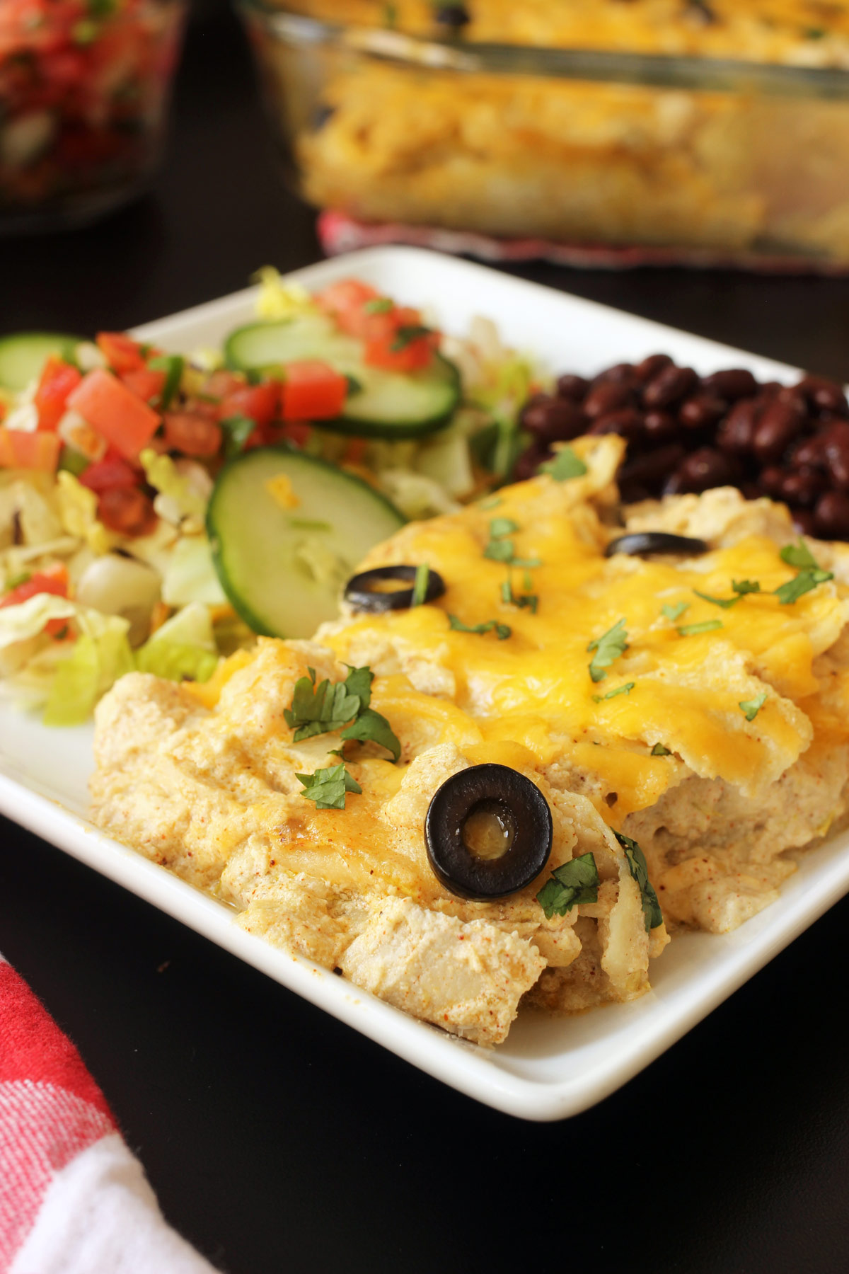 plate of enchilada bake with salad and beans
