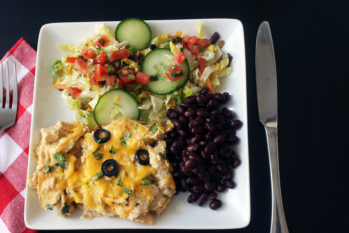 plate of enchilada bake with sides, fork, and knife