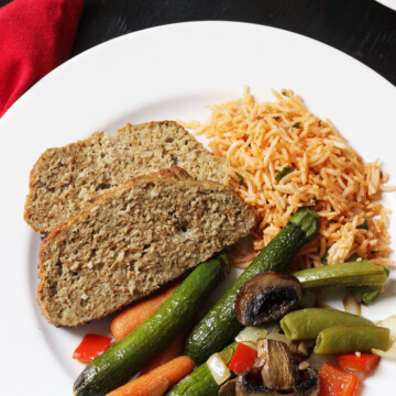 A plate of vegetables, rice, and meatloaf