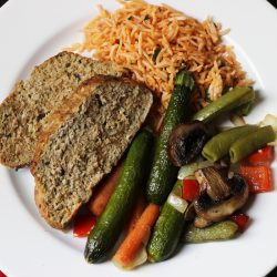 A plate of meatloaf, rice, and vegetables