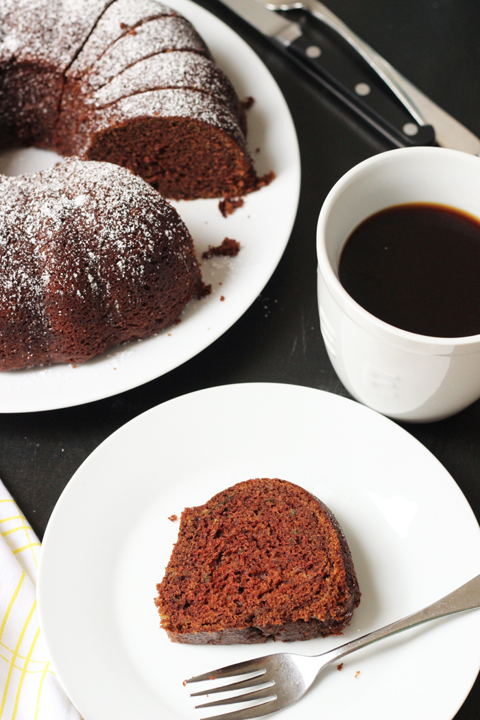 slice of chocolate zucchini cake on a plate, and a cup of coffee