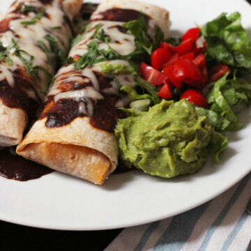 A plate of red burritos with guacamole