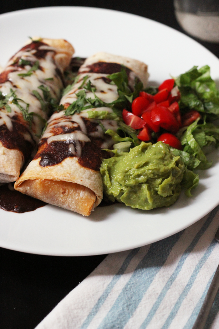 chimichangas on a plate with enchilada sauce and toppings on the side