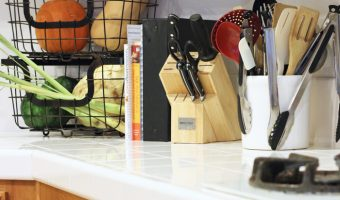 A kitchen counter with utensils and cookbooks