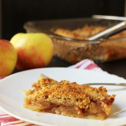 slice of slab apple pie on plate next to apples
