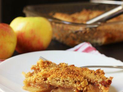 slice of slab apple pie on plate next to apples