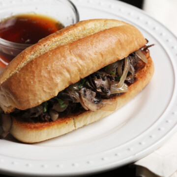 A plate with French dip sandwich and jus