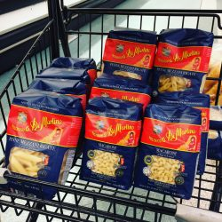 bags of pasta in grocery cart