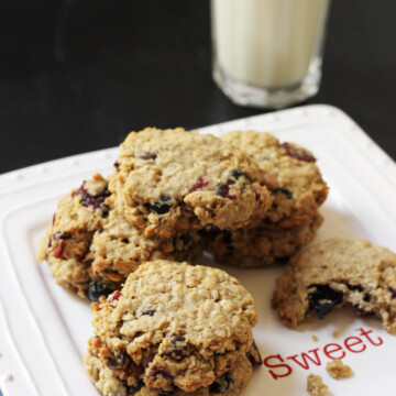 oatmeal cookies on a white plate with glass of milk