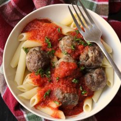 A bowl of pasta with Meatballs and sauce