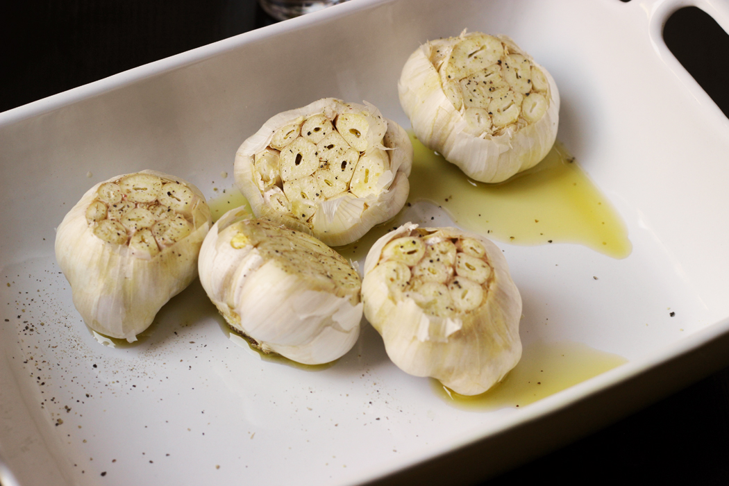 A baking dish of garlic heads with olive oil