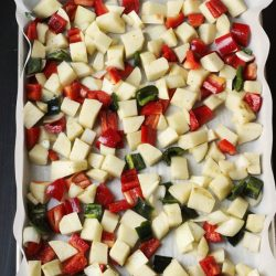 raw potato and pepper cubes on lined tray