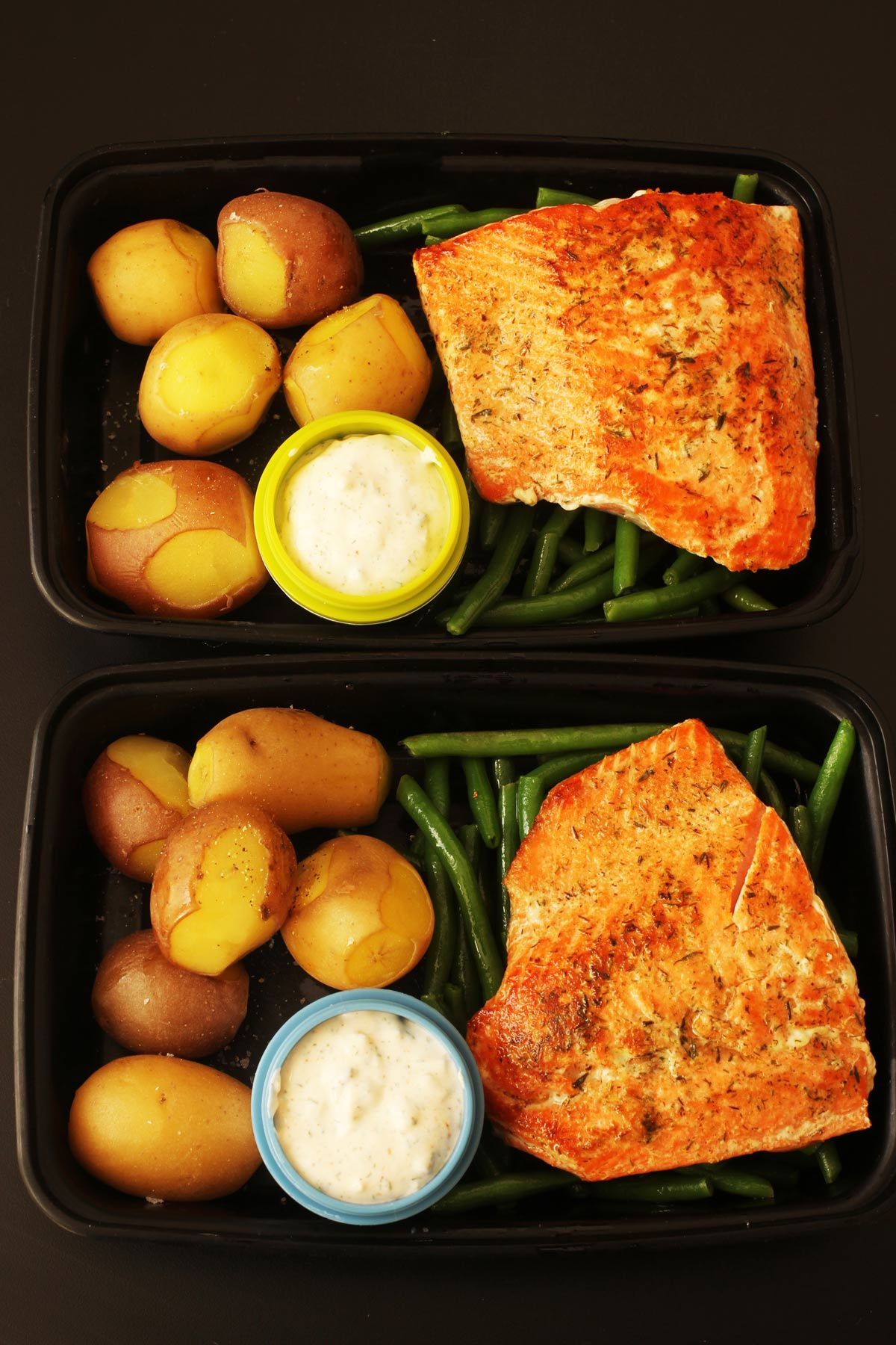 meal preps of fish with cups of tartar sauce