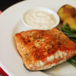 cooked salmon on dinner plate with dish of tartar sauce