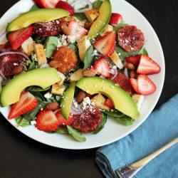 spinach salad topped with fruit