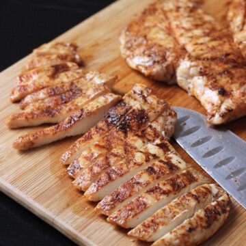 chicken breasts sliced on wooden cutting board