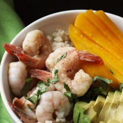 A bowl of shrimp with mango and avocado