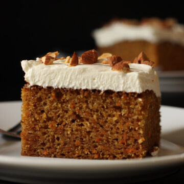 square of carrot cake topped with cream cheese frosting.