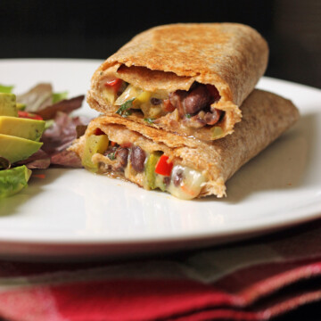 black bean and pepper wrap cut open and stacked on a plate