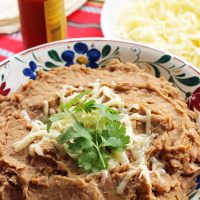 bowl of refried beans with bowl of cheese and bottle of hot sauce