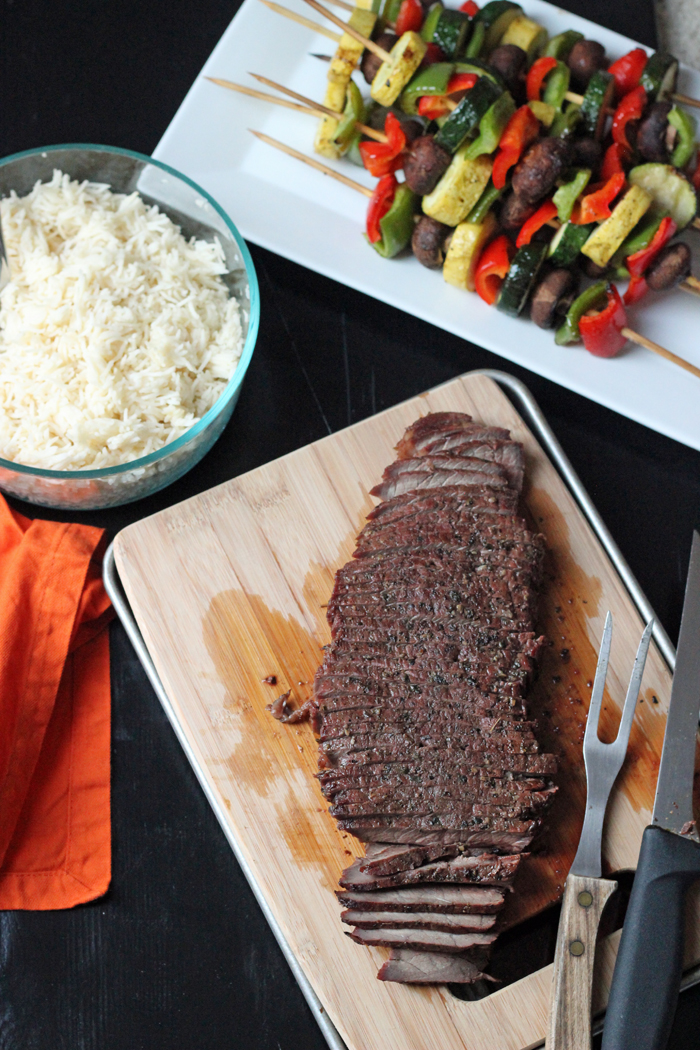 grilled steak on cutting board with rice and kabobs platters