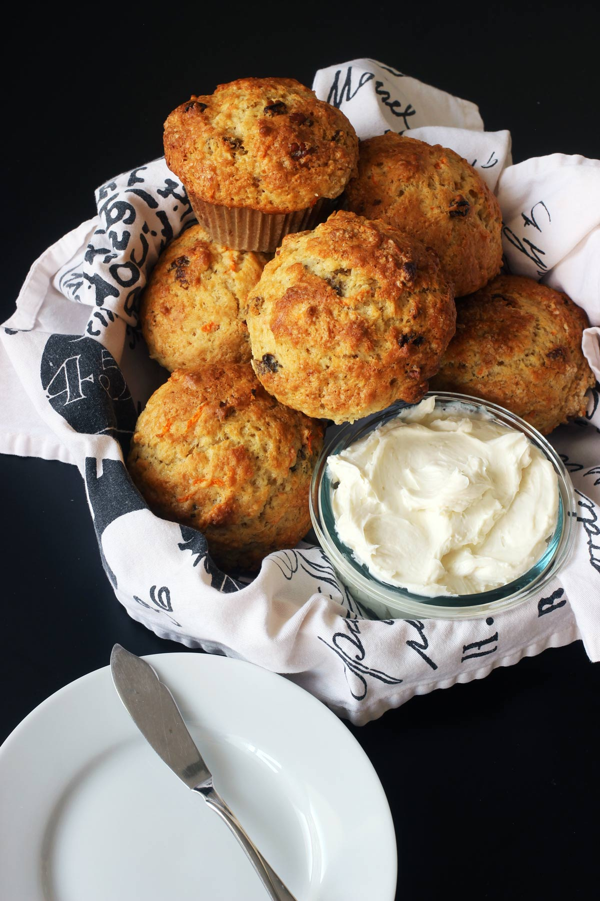 towel-lined basket of carrot muffins with cream cheese topping