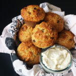 carrot muffins in basket with bowl of cream cheese