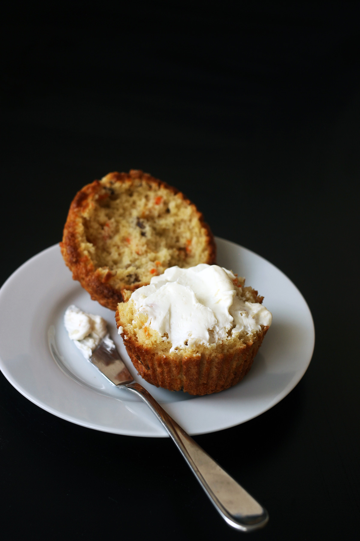 split carrot muffin with cream cheese spread on half