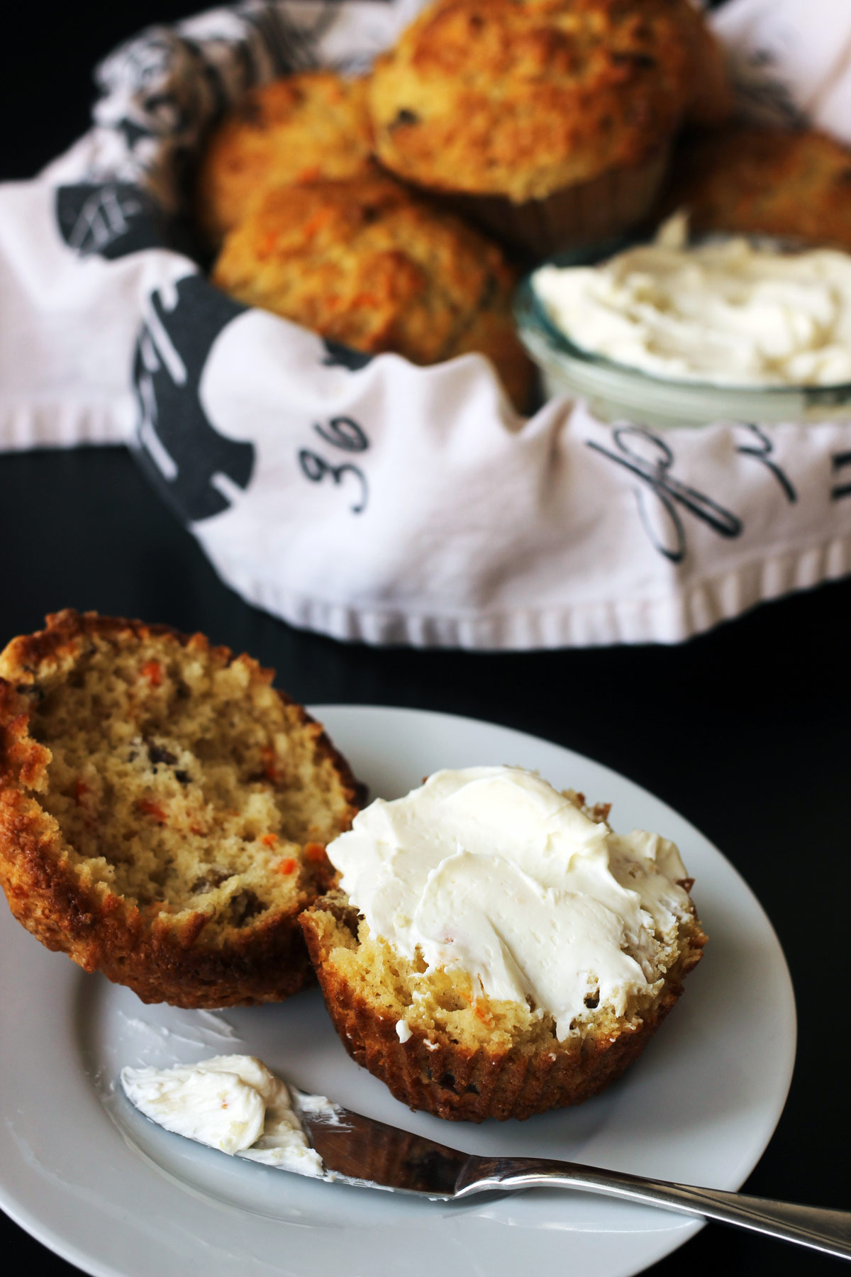 muffin on small plate with cream cheese spread