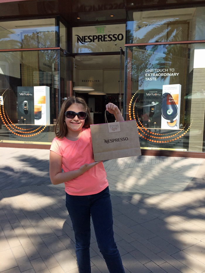 A girl standing on a sidewalk with a Nespresso bag