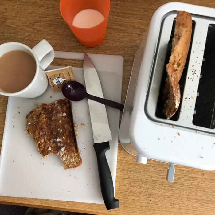 toaster next to prepped toast and tea