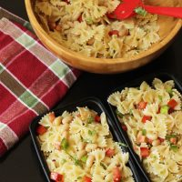 bowl of bowtie pasta salad with meal prep boxes