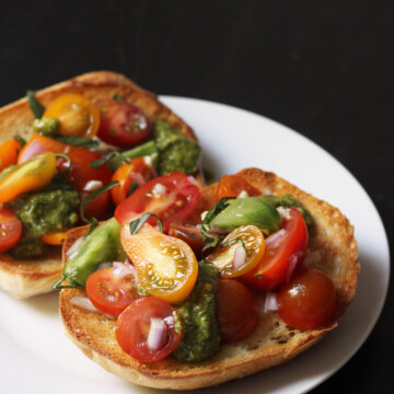 A plate of bruschetta toasts piled with tomatoes