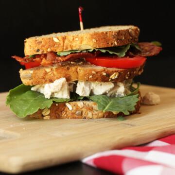 triple decker chicken salad club sandwich on board with checked cloth