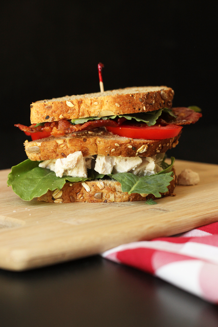 triple decker chicken salad club sandwich on board with checked cloth